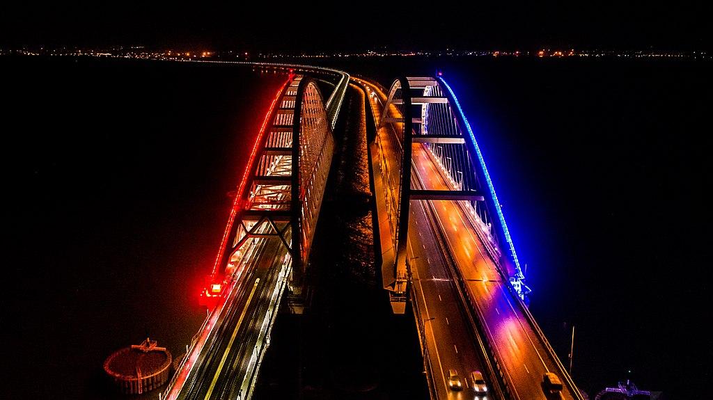 Крымский мост вечером 18 декабря 2019 года. Арки автомобильного (справа) и железнодорожного переходов с подсветкой. Фото: Росавтодор