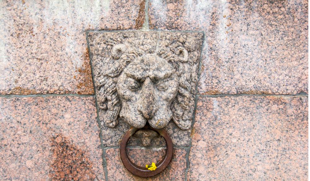 Гранитные львы-барельефы с металлическими кольцами в зубах