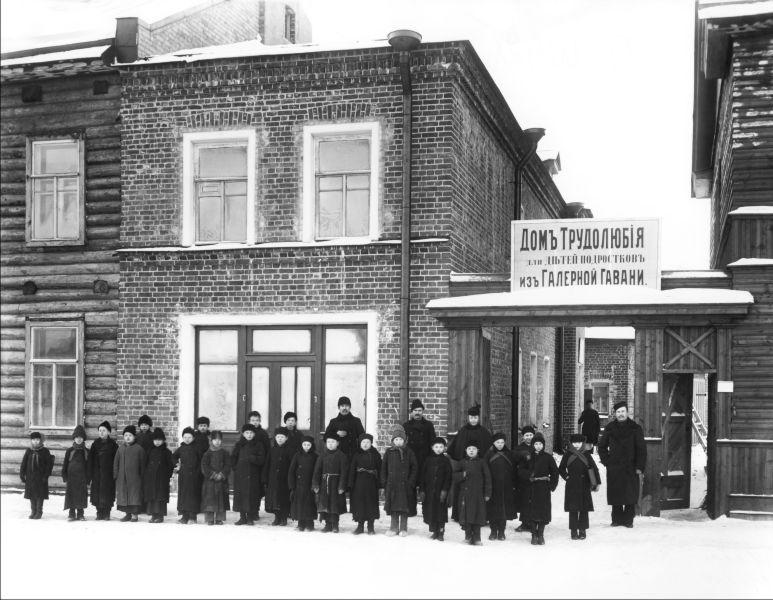 Группа мальчиков у здания Дома трудолюбия для детей-подростков Галерной гавани. Санкт-Петербург. Начало 1900-х. Фото ателье К. К. Буллы (Wikimedia Commons)