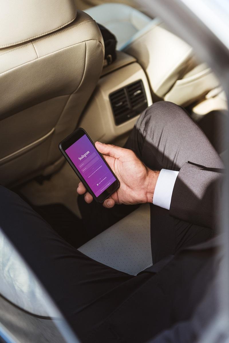 Обрезанный образ бизнесмена, держащего смартфон с загруженной страницей Instagram в автомобиле — Фото автора AllaSerebrina