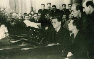 На фотографии из архива Дмитрий Шостакович за роялем показывает музыкантам Филармонического оркестра ЗКР свою Девятую симфонию. Из-за спины автора, стоя с папиросой, внимательно вглядывается в партитуру Евгений Мравинский