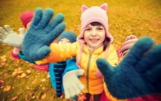 Счастливые дети машут руками в осеннем парке